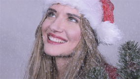Cute girl in santa claus hat with tree branches enjoying snowfall. stock footage