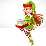 Cute girl Santa elf with gifts sit on banner Stock Photography