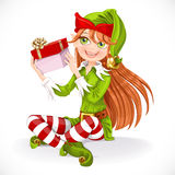 Cute girl Santa elf sit on floor hold gift Stock Photos