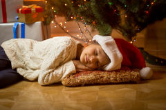 Cute girl in Santa hat fell asleep under Christmas tree Royalty Free Stock Photography