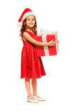 Cute girl in Santa hat hold huge present Stock Photography