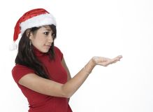 Cute Girl In Santa Hat Holding... Cute Girl Looking at her hand which is Holding stock photo