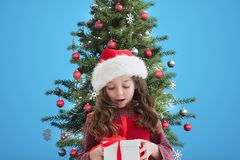 Cute girl in santa hat looking at christmas gift Stock Photo