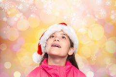 Cute girl in santa hat pretending to be amazed Stock Photo