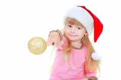 Cute girl in santa hat throing gold ball Royalty Free Stock Photos