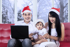 Cute girl in santa hat using laptop with family Stock Photography