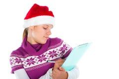 Cute girl with Santa hat writing something Stock Image