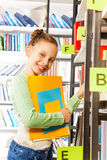 Cute girl searching books on the bookshelf Royalty Free Stock Images