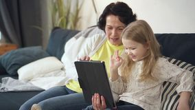 Cute girl and senior woman is sitting on couch and talking with family. stock footage