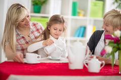 Cute girl serving tea her mom and grandma Stock Photo