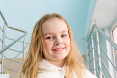 Cute girl seven years old. Portrait of cute girl with blond hair in white royalty free stock photography