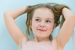 Cute girl seven years old. Portrait of cute girl with upwards hands and blond hair royalty free stock images