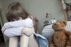 Cute girl seven years old sitting on bed and cryi royalty free stock photo