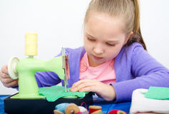 Girl sewing. Cute girl sewing on a sewing machine at home Stock Photo