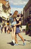 Cute girl in jean shorts jumping to bearded man. Cute girl in jean shorts jumping to bearded men sunny, summer day. Stylish couple in love hugging and kissing in stock image