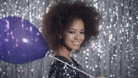 Cute girl in shiny elegant shirt posing with purple balloon in studio. stock video footage