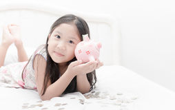 Cute girl show piggybank on bed Royalty Free Stock Image