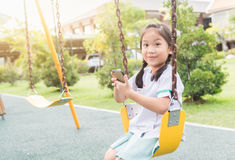 Cute girl show smart phone in children playground Royalty Free Stock Images