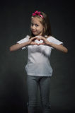 Cute girl showing heart shaped sign Stock Photos