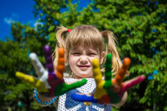 Cute girl showing her hands painted in bright colors. Hand prints Stock Photo