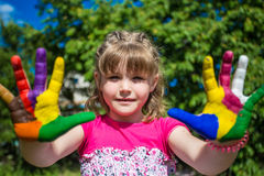 Cute girl showing her hands painted in bright colors. Hand prints Stock Photos