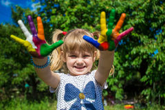Cute girl showing her hands painted in bright colors. Hand prints Royalty Free Stock Image
