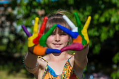 Cute girl showing her hands painted in bright colors. Hand prints Royalty Free Stock Images