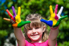 Cute girl showing her hands painted in bright colors. Hand prints Royalty Free Stock Photography