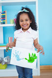 Cute girl showing paper with colored hands prints on it stock images