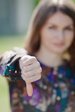 Cute girl showing thumb down. Focus on foreground Royalty Free Stock Photo