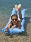Cute girl showing thumb's up sign on sea Stock Photos