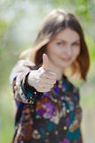 Cute girl showing thumb up. Focus on foreground Royalty Free Stock Photos
