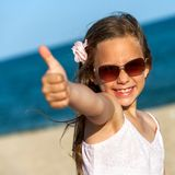 Cute girl showing thumbs up on beach. Royalty Free Stock Images