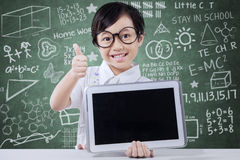 Cute girl shows tablet and thumb up in class Royalty Free Stock Photos