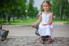 Cute girl sit on a duck figure of iron and having Stock Photos