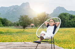 Cute girl sit and relax on chair and yellow flower background Stock Photography