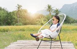Cute girl sit and relax on chair and yellow flower background,. Cute girl sit and relax on chair and yellow flower background, travel concept Royalty Free Stock Images