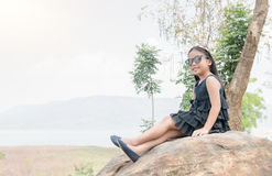 Cute girl sit on rock on dam background Royalty Free Stock Image