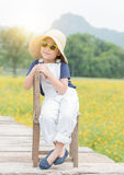 Cute girl sit on wood chair with nature background. Cute girl sit on wood chair and yellow flower background, travel concept Stock Photos
