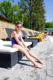 Cute girl sits on deck chair near pool Stock Photos