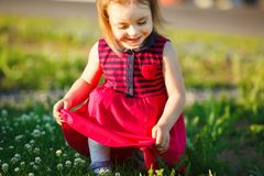 Cute girl sits on a green field and holds her dress. Cute baby in good mood Royalty Free Stock Images
