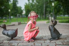 Cute girl sits next a duck figure of iron and Stock Photography