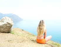 Cute girl sitting. On a hill and watching the sea Royalty Free Stock Photos