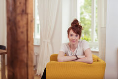Cute Girl Sitting on Armchair with Arms Crossed Royalty Free Stock Image