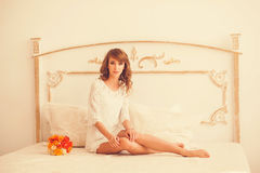Cute girl sitting on a bed in a dress Royalty Free Stock Photo
