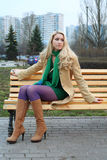 Cute girl sitting on a bench. Cute girl in purple tights sitting on a bench stock photo