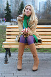 Cute girl sitting on a bench. Cute girl with red nails in purple tights sitting on a bench royalty free stock image