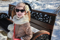 A cute girl sitting on a bench in winter Stock Images
