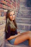 Cute girl sitting on brick steps Stock Photos