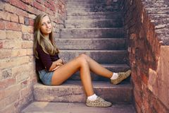 Cute girl sitting on brick steps Royalty Free Stock Photos